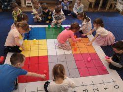 Dzieci układają kolorowe kubeczki dywanie w kształcie koła