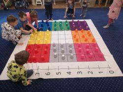 Dzieci układają kolorowe kubeczki na macie do kodowania