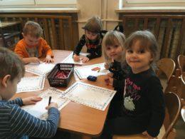Dzieci siedzą przy stoliku, kolorują obrazki kota