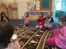 Dzieci siedzą na dywanie w kole, patrząc na lusterka