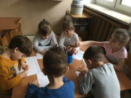 Dzieci rysują przy stoliku dinozaury