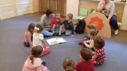 Dzieci siedzą w kole słuchając mamy czytającej książkę