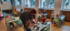 zdjęcie dzieci pracujaych przy stolikach