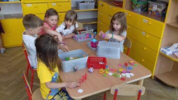 dzieci układają klocki przy stole