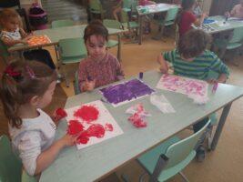 dzieci malują palcami farbą