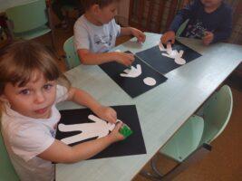 Dzieci przy stole nakleją sylwety człowieka