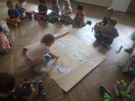 Dzieci wyklejają pracę plastyczną mrówki na podłodze - Mrówka