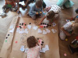 Dzieci wykonujące wspólnie prace plastyczną na podłodze