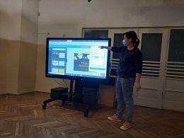Zdjęcie nauczycielki objaśniającej coś na monitorze