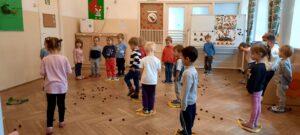 Zdjęcie dzieci bawiących się kasztanami w sali