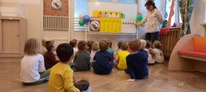 zdjęcie dzieci słuchających nauczycielki przy tablicy