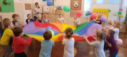 zdjęcie dzieci bawiących się chustą animacyjną z balonami