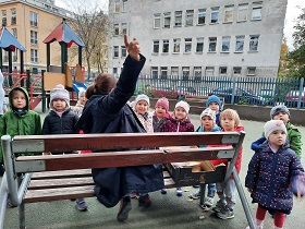 zdjęcie dzieci i nauczycielki w ogrodzie przedszkolnym słcuhających ciekawostek o drzewie