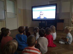 Zdjęcie dzieci oglądających nagranie bajki czytanej przez Panią Dyrektor