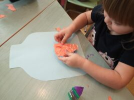 zdjęcie dziecka wyklejającego z papieru
