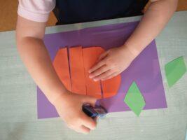 zdjęcie dziecka wyklejającego pracę plastyczną