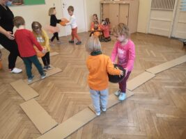 zdjęcie dzieci bawiących się w parach z balonami na kładce z kartonu