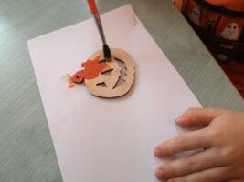 zdjęcie dziecka malującego drewnianą dynię