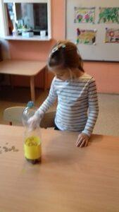 zdjęcie dziewczynki wrzucającej pieniądze do skarbonki