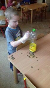 zdjęcie chłopca wrzucającego pieniądze do skarbonki
