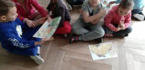 Zdjęcie dzieci oglądających rysunki na podłodze