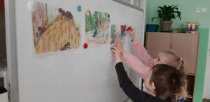 Zdjęcie dzieci oglądających rysunki mrowiska na tablicy