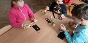 Zdjęcie dzieci pracujących przy stołach