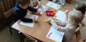 Zdjęcie dzieci wykonujących papierowy sznur korali
