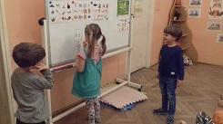 zdjęcie dzieci stojących i rysujących coś na tablicy