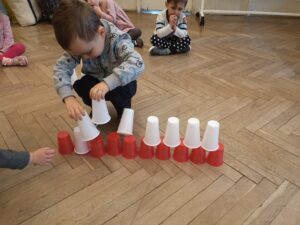 zdjęcie dziecka układającego kubeczki