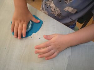zdjęcie dziecka ugniatającego ciastolinę