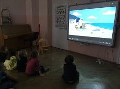 zdjęcie dzieci oglądających bajkę na tablicy multimedialnej
