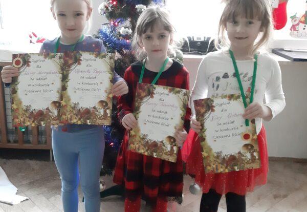 Zdjęcie dziewczynek prezentujących dyplomy za udział w konkursie plastycznym