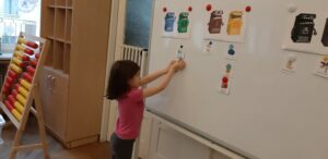 Zdjęcie dziecka wykonującego segregację śmieci na tablicy