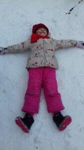 zdjęcie dziecka robiącego aniołka na śniegu