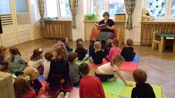 Zdjęcie dzieci siedzących na macie i słuchających bajki