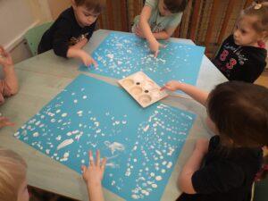 zdjęcie dzieci malujących palcami śnieg