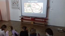 Zdjęcie dzieci oglądających prezentację na tablicy multimedialnej