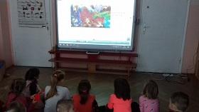 Zdjęcie dzieci oglądających prezentację na tablicy interaktywnej
