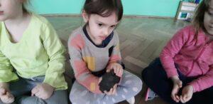 zdjęcie dziecka oglądającego kawałek wulkanu