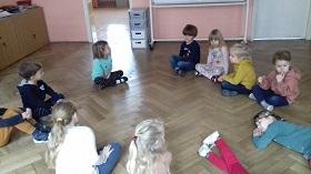 Dzieci siedzące w kółku, na podłodze w sali. w siadzie skrzyżnym. Dwójka dzieci leży