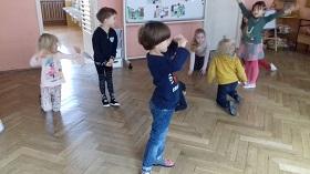 Dzieci wykonujące różne ruchy - klęczenie, stanie, wyciąganie rąk w górę.