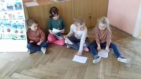 Dzieci siedzące na podłodze, trzymające w rękach kartki bądź kładące je na podłodze