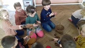 Dzieci siedzące w grupce na podłodze. Trzymające w rękach figurki z drewna, pokazując je sobie nawzajem. Obok na podłodze stoi koszyk z korą.