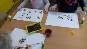 Dzieci trzymające pędzle lub korę w dłoni. Na stole znajdują się prace z naklejoną korą drzewa, klej, kora i plastikowa filiżanka.
