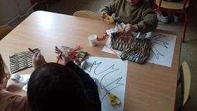 Dzieci trzymające pędzle w ręku i malujące po kartce papieru, znajdującej się na stole. W tle dziecko wycina nożyczkami brązową bibułę.
