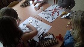 Dzieci przyklejające srebrną bibułę na kartkę papieru, leżącą na stole. Obok siedzi dziecko z pędzlem w ręku. W tle widoczna jest praca, z przyklejoną brązową bibułą.