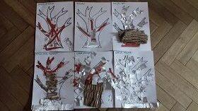 Sześć kartek papieru leżących obok siebie na podłodze, przedstawiających drzewa. Oklejone są srebrną i brązową bibułą oraz brązowym kartonem.