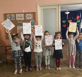 Dzieci trzymające w rękach dyplomy, stojące obok siebie na sali