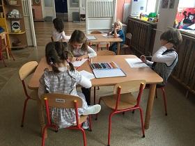 Dzieci siedzące na krzesełkach przy stole. Kolorujące prace kredkami
